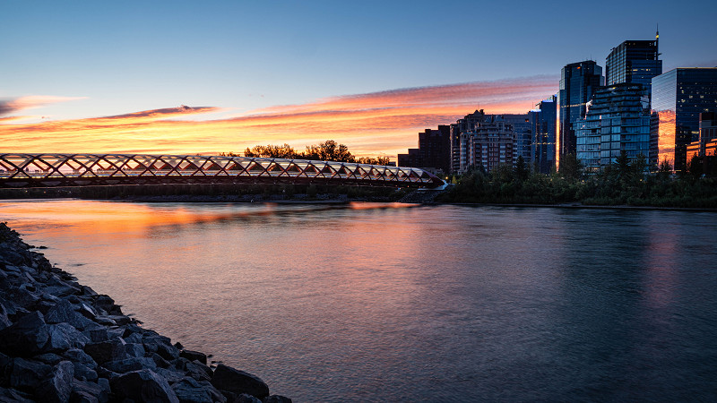 The sun rises early in the August morning at the Peace Bridge in Calgary, Alberta, Canada