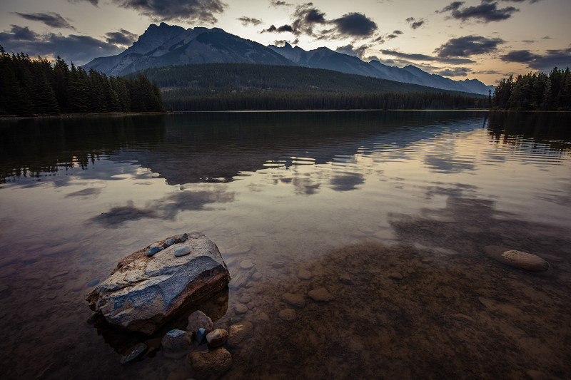 The sun tries to peek over Mt. Rundle - As Mt. Rundle overlooks Two Jack Lake, the sun tries to peek its head over the giant peak in Banff National Park, Alberta, Canada