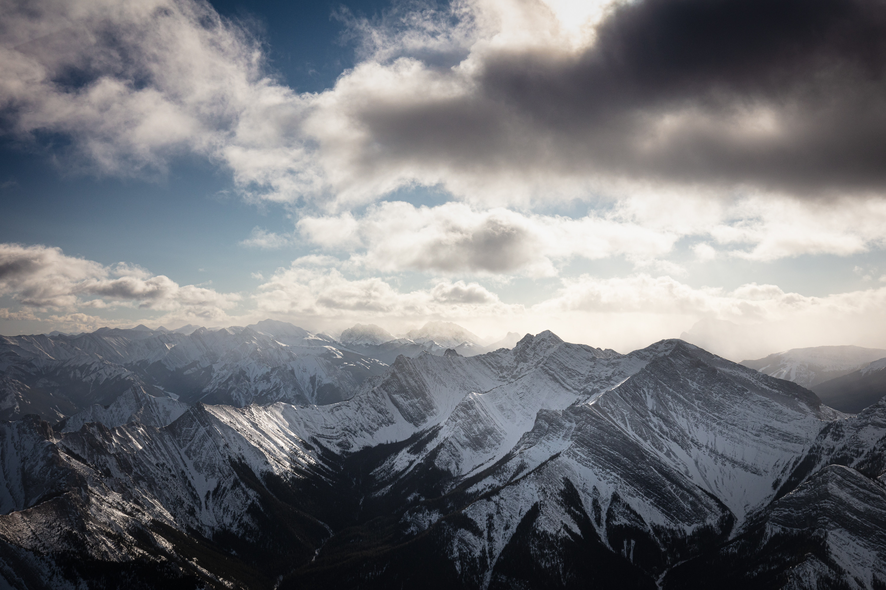 Shot during a very bumpy ride in the Mooney, the sun pokes through the clouds hanging over the eastern edge of the Canadian Rockies